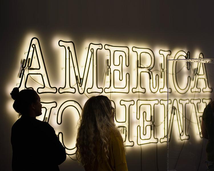 students look at America sign at the Jordan Schnitzer Museum of Art