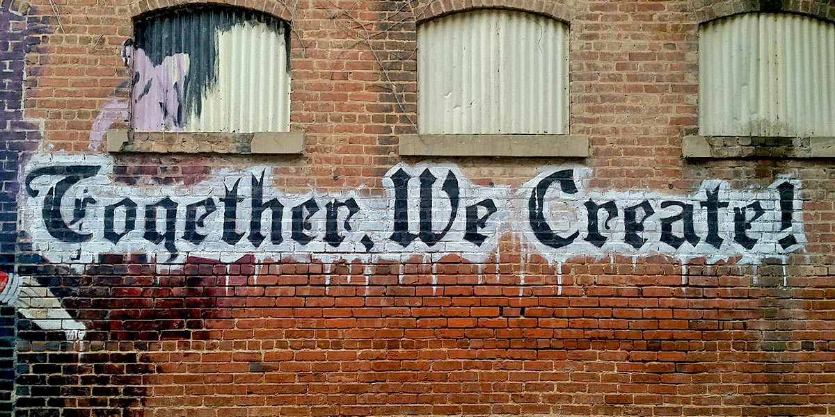 Graffiti that says Together We Create on brick wall