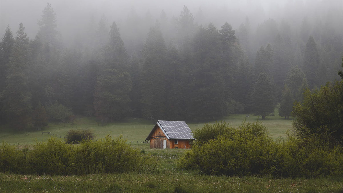 cabin in meadow with solar panels