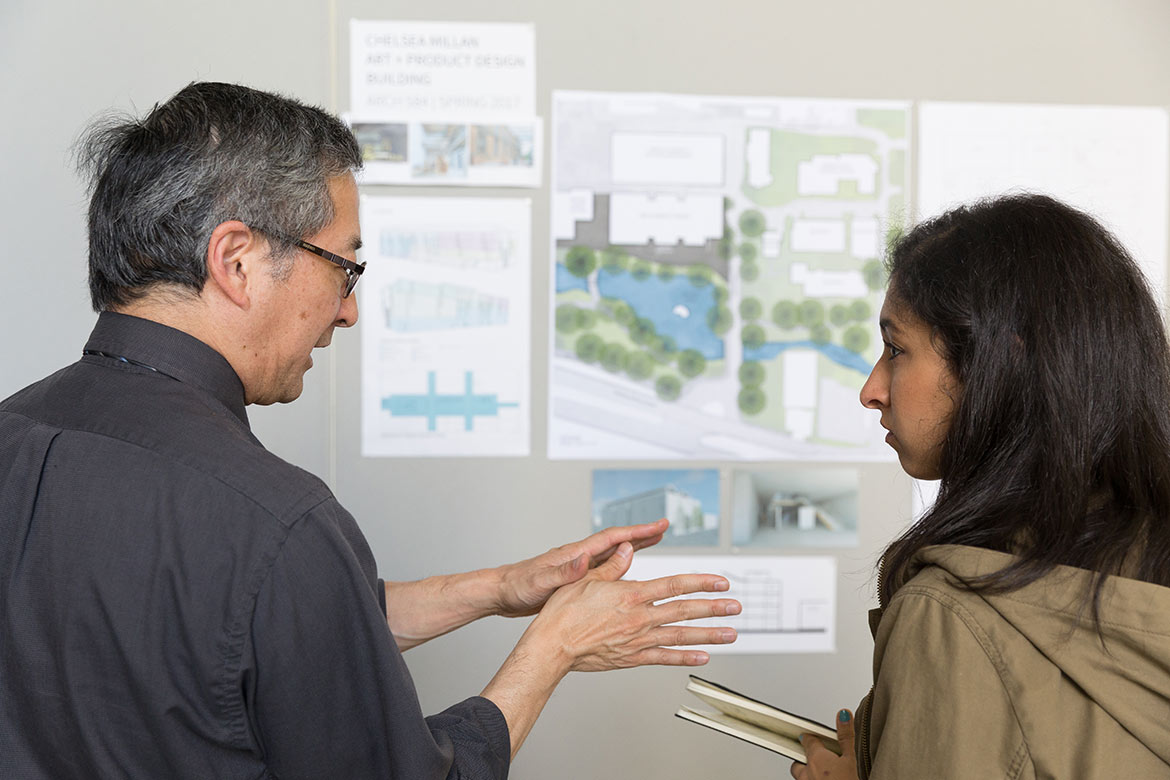 two people talk with student work in background