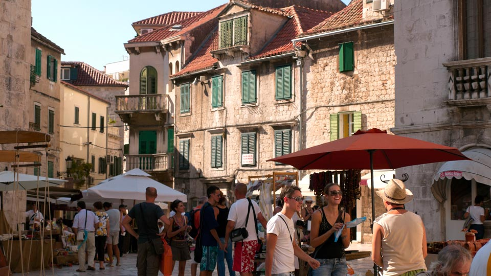 people in courtyard with stone buildings during Croatia Field School