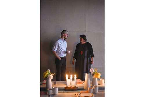 Two people standing at candle lit table