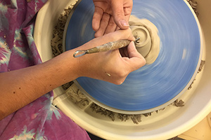 student works on ceramicware