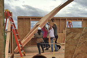 Students raise a wall during construction of the OregonBILDS house in 2016