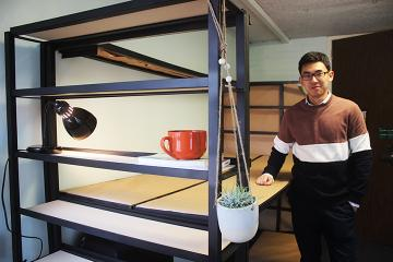 Zihan Wang beside the bunk bed in his group's residence hall room design