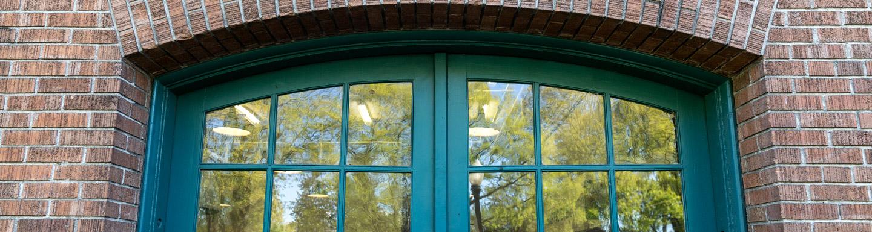 green doors in brick building