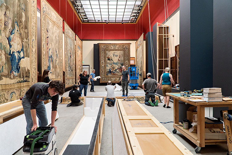 people work to hang tapestries