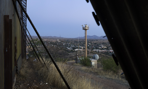 View into Nogales from the Border Fence (with camera tower), Arizona.