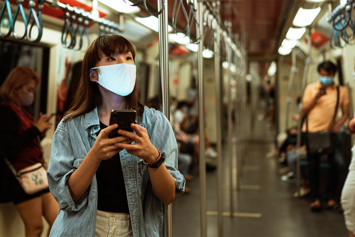 Women in mask with others in the subway