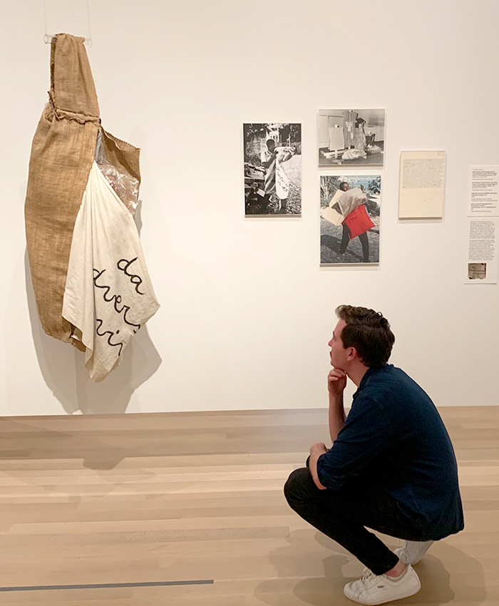 Liam Maher crouches at an art exhibition