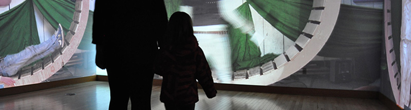 silhouette of adult and child looking at art projected on walls