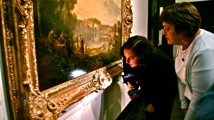 two people inspect framed art at museum with flashlight