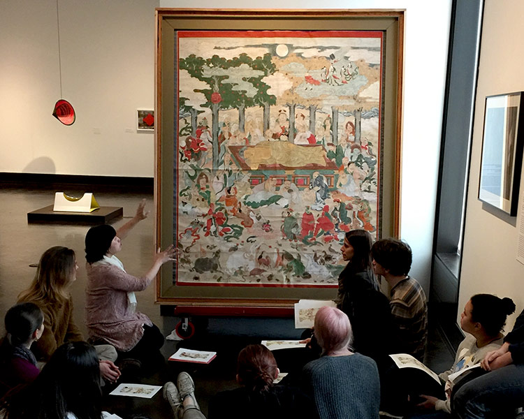 students learn about artwork depicting the death of Buddha