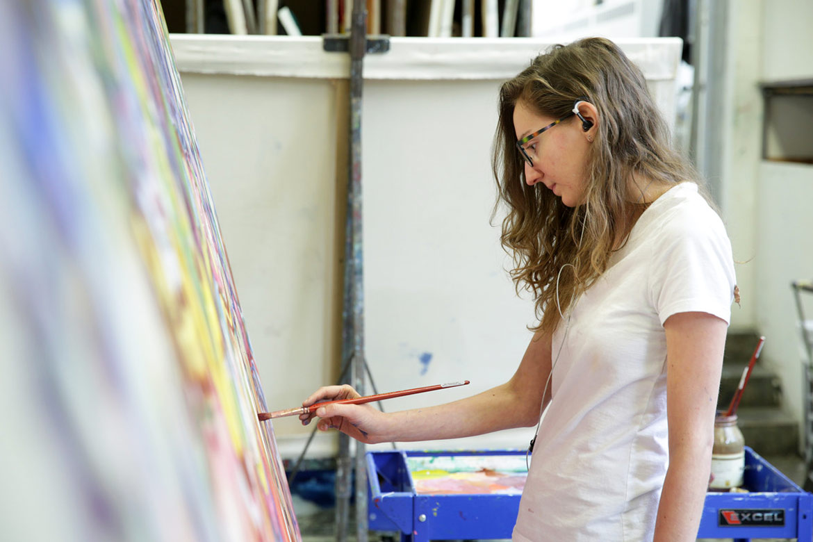 student works on large painting