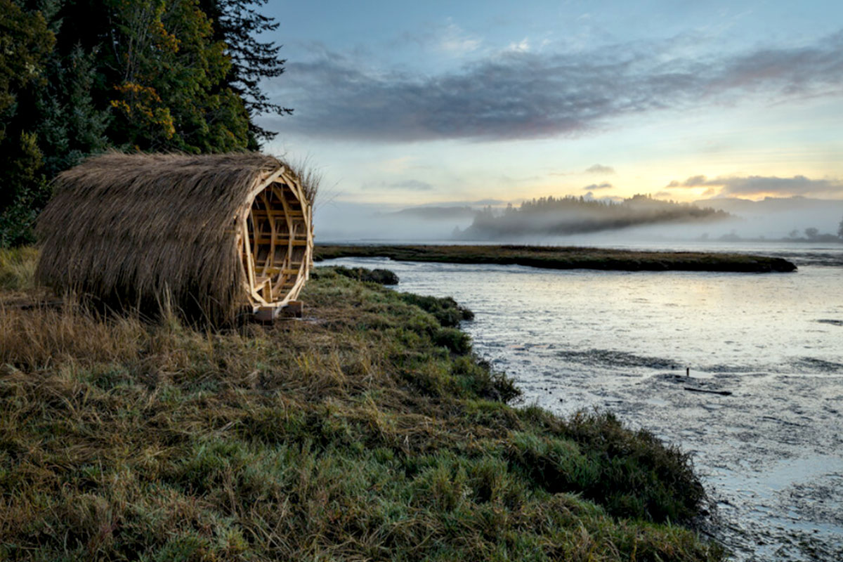 wooden cylinder structure in a field on a body of water