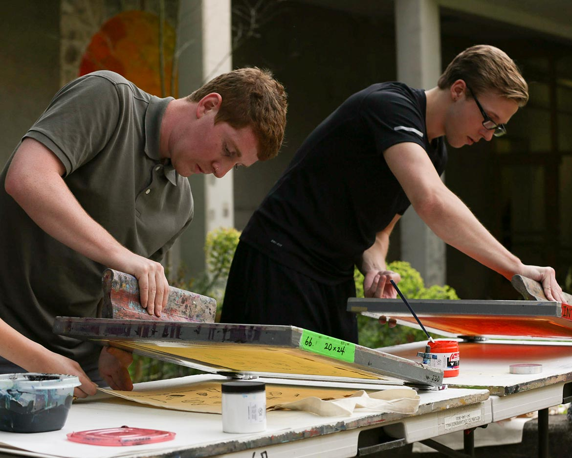 students work with yellow and red ink while making prints