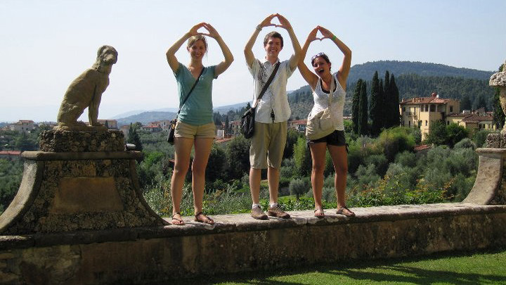 three students make O with hands while visiting Rome