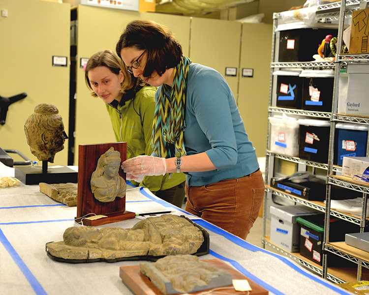 two people inspect sculptural artifacts at the Jordan Schnitzer Museum of Art