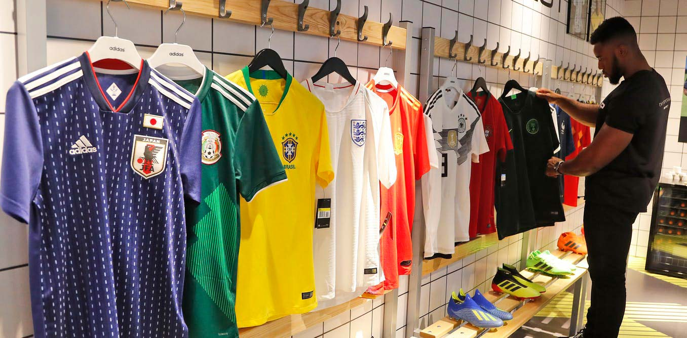 person looks at soccer jerseys on display
