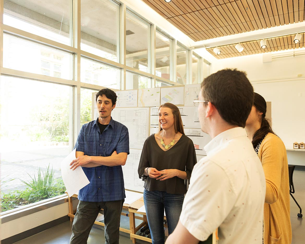 students talk while displaying work