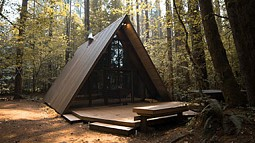 photo of an A-frame house in a forest