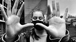 Black and white photo of woman holding up a mirror