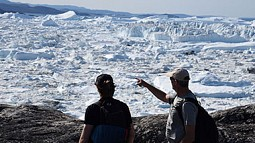 Photo of two people looking at glaciers