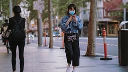 woman wearing mask walking down city street