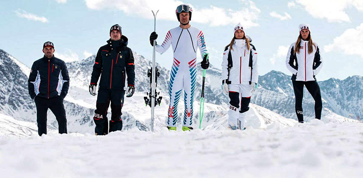 people stand in snow wearing Winter Olympics gear. Image source: The Conversation.
